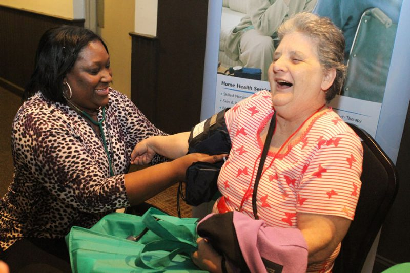 Woman provider taking blood pressure of client. Both women are smiling.