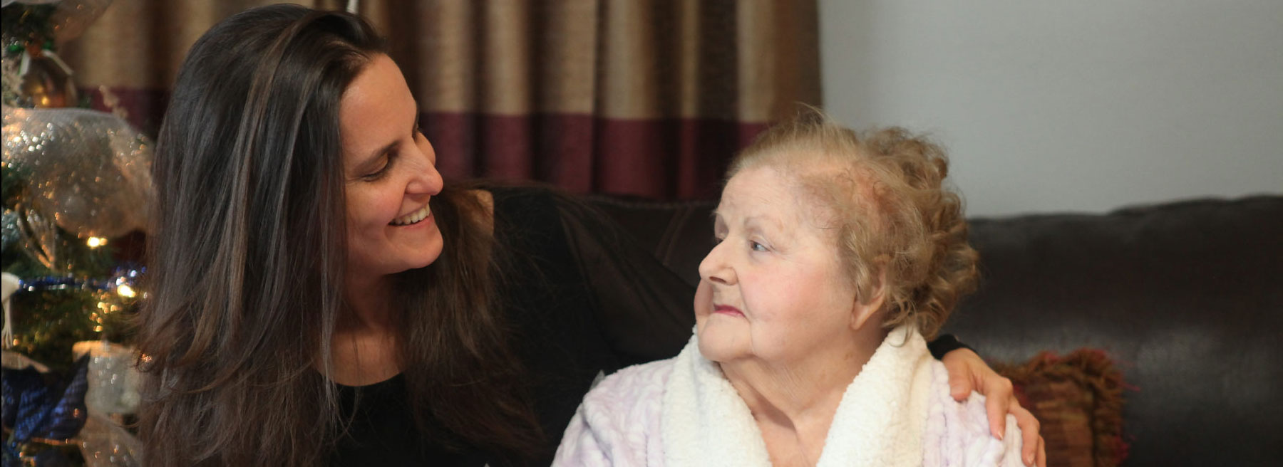 Photo of younger woman caregiver with arms around elderly woman.